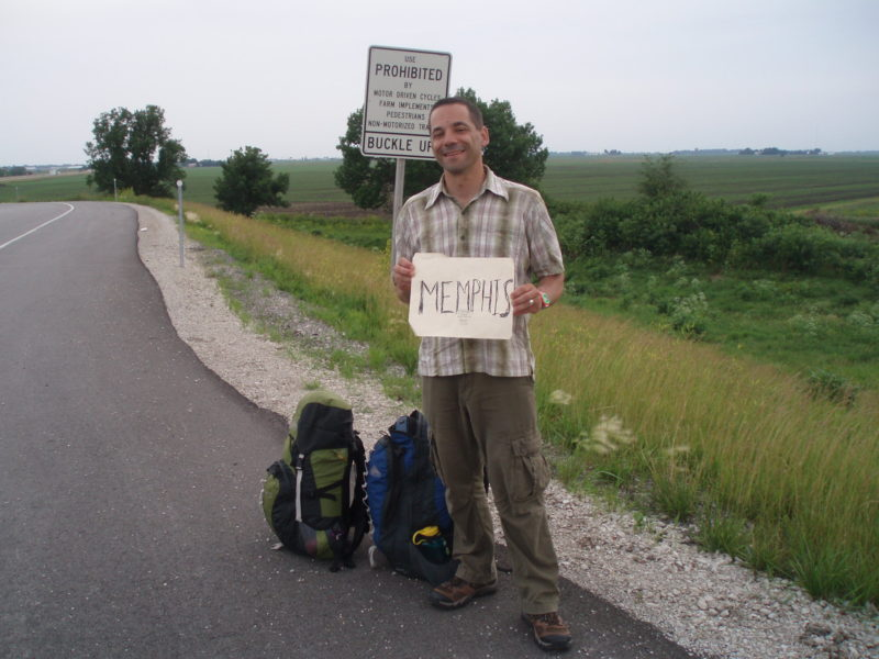 """Man standing on the roadside with backpacks and a sign saying """"Memphis"""" with green fields behind him."""