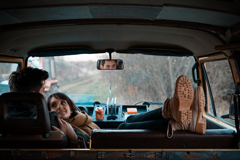 Man and woman relaxing in front seat of a van.